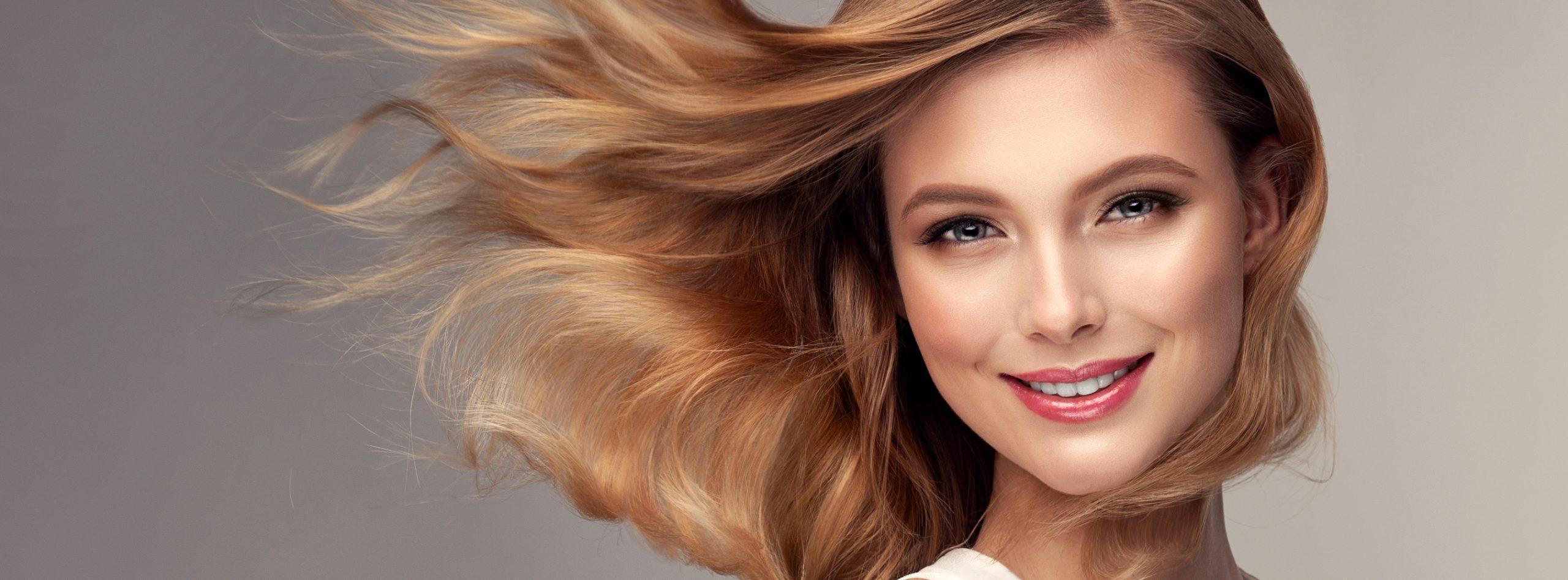 Lächelnde Frau mit wehenden blonden Haaren
