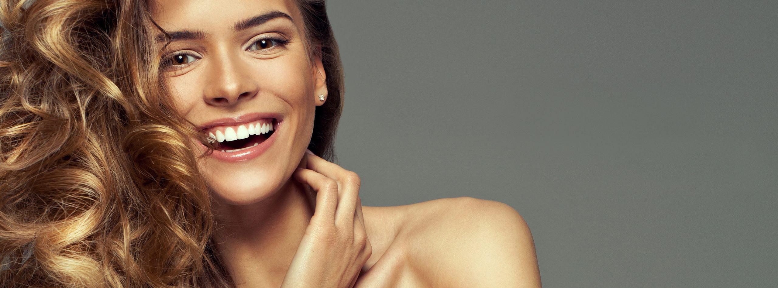Frau mit langen, blonden Haaren und strahlendem Lächeln